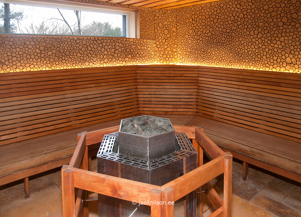 Sauna room with wooden benches and central heated stove or stone in Viimsi Spa Hotel in Tallinn, Estonia
