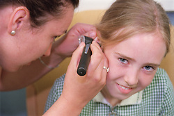 Young girl having ear examined by audiologist using otoscope at aural care centre,