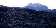 City lights on ridge with snow capped mountain in distance, Our Lady of Peace, Nuestra Señora de La Paz