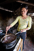 The daughter-in-law of rice farmer Nguyen Van Theo cooks pork at their shared homestead in Tho Quang village, Vietnam. (From the book What I Eat: Around the World in 80 Diets.)  Nguyen Van Theo and his family still eat traditional Vietnamese foods.