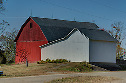 08 September 2006  a sizeable red framed barn with a hayloft stands behind a white barn and machine shed near a road in the fall in Parke County Indiana.<br /> <br /> This image was produced in part utilizing High Dynamic Range (HDR) processes.  It should not be used editorially without being listed as an illustration or with a disclaimer.  It may or may not be an accurate representation of the scene as originally photographed and the finished image is the creation of the photographer.