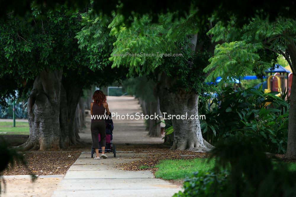 Israel, Kibbutz Mishmarot A woman walks with a stroller
