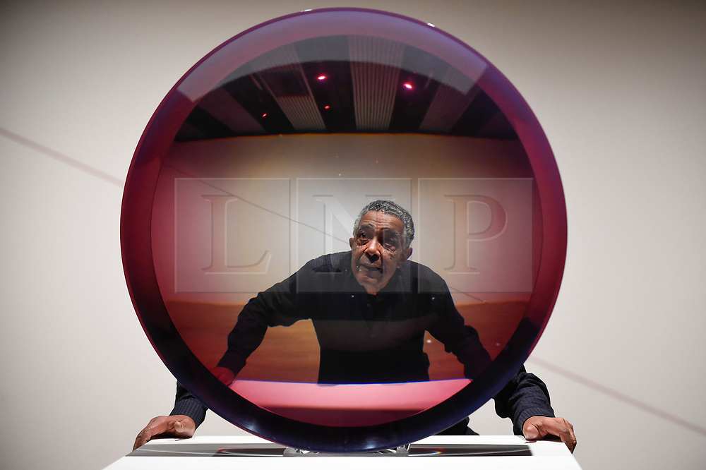 "© Licensed to London News Pictures. 25/09/2018. LONDON, UK. Artist Fred Eversley poses with his work ""Untitled (Parabolic Lens)"", 1971. Preview of ""Space Shifters"" at the Hayward Gallery, an exhibition which features artworks by 20 leading international artists that disrupt the visitor's sense of space and alter their perception of their surroundings.  The show runs 26 September to 6 January 2019.  Photo credit: Stephen Chung/LNP"