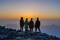 A back view of a group of mountaineers as seen in the twitlight contemplating the sunset from the moraine close to Aiguille du Gouter, on the classical route from Les Houches to the summit of Mont Blanc, France.