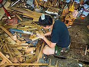 02 NOVEMBER 2016 - BANGKOK, THAILAND:  GOB, who now runs the family spirit house workshop, uses small handsaw to cut teak wood for a spirit house. There used to be 10 families making traditional spirit houses out of teak wood in Ban Fuen, a community near Wat Suttharam in the Khlong San district of Bangkok. The area has been gentrified and many of the spirit house makers have moved out, their traditional wooden Thai houses replaced by modern apartments. Now there is just one family making the elaborate spirit houses. The spirit houses are made by hand. It takes three days to make a small one and up to three weeks to make a large one. Prices start at about $90 (US) for a small one. The largest, most elaborate ones can cost over $1,000 (US). Almost every home and most commercial buildings in Thailand have a spirit house, which is a shrine to the protective spirit of a the land. Spirit houses are also common in Burma, Cambodia, and Laos.       PHOTO BY JACK KURTZ