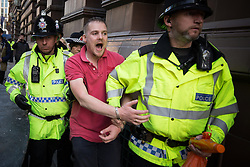 © Licensed to London News Pictures . 04/10/2015 . Manchester , UK . Police detain a man outside the conference venue . A demonstration against the Conservative government , organised by The People's Assembly , at Castlefield Bowl in Manchester , during the first day of the Conservative Party Conference in Manchester . Photo credit: Joel Goodman/LNP