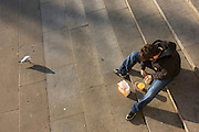 Lunchtime man eating outside on pavement in Trafalgar Square watched by seagull.