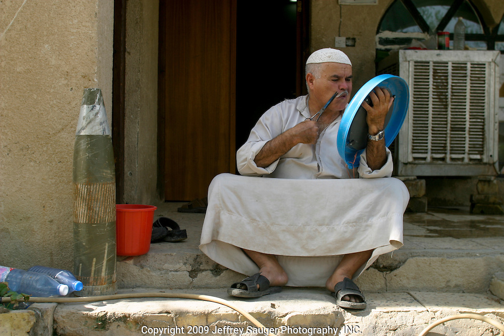 Saleh Dawoud, a Shiite Iraqi, trims his mustache at his home in Nasiriyah, Iraq, on August 13, 2003. At left is the casing of bomb that injured his wife and damaged their home.