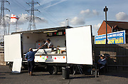 A lorry driver is handed his change after buying a burger at a fast food trailer in Grays, Essex England. The large man has parked his vehicle in a truck stop car park for an early evening food snack. The lady serving him works in an outside mobile burger bar that stands at this popular spot for working men as they pass-by this industrial corridor on the River Thames. Meanwhile, the serving woman's friend sits sunning himself and scratching his head beneath a film poster for the British comedy 'Run Fat Boy, Run' with actor Simon Pegg. Further in the distance, the English Cross of St George flutters and a line of electricity pylons take a transmission cables into central London, taking power into the capital. This south Essex town in the Thames Gateway, is the location for dramatic increases of new housing developments.