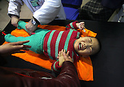 Three-year-old Gao Xiang cries from pain under the massage aimed to help her stiff legs, damaged since birth, while her mother holds her hand, in Cerebral Palsy Hospital, in Taiyuan, Shanxi province, China, on November 15, 2007. Gao Xiang is holding a 1 Chinese Yuan (0.14 US$) banknote in her right hand that her mother gave her as a reward if she kept quiet. China's rate of birth defects had risen from 104.9 per 10,000 births in 2001, to 145.5 in 2006, China's National Population and Family Planning Commission said in a report on its web site (www.chinapop.gov.cn). China's coal-rich northern province of Shanxi, a centre of noxious emissions from large-scale coke and chemical industries, had the highest rate of birth defects, Xinhua news agency said. Photo by Lucas Schifres/Pictobank