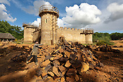 Worker throwing cut stones onto piles at the quarry, and behind, the Great Tower or Tour Maitresse, Chapel Tower and Corner Tower (left-right), still under construction, at the Chateau de Guedelon, a castle built since 1997 using only medieval materials and processes, photographed in 2017, in Treigny, Yonne, Burgundy, France. The Guedelon project was begun in 1997 by Michel Guyot, owner of the nearby Chateau de Saint-Fargeau, with architect Jacques Moulin. It is an educational and scientific project with the aim of understanding medieval building techniques and the chateau should be completed in the 2020s. Picture by Manuel Cohen