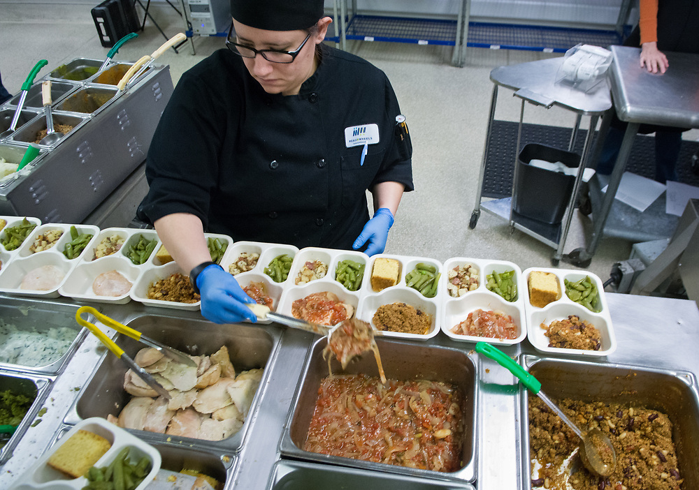 Soozi Becerra, center, fills trays with food at the Meals on Wheels kitchen in Albuquerque, N.M., Friday, March 24, 2017. Meals on Wheels delivers about 550 meals a day. (Marla Brose/Albuquerque Journal)