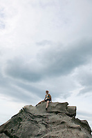 Woman sitting atop granite rock&#xA;<br />