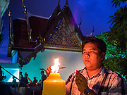 20 NOVEMBER 2015 - BANGKOK, THAILAND: A man lights candles during the temple fair at Wat Saket. Wat Saket is on a man-made hill in the historic section of Bangkok. The temple has golden spire that is 260 feet high which was the highest point in Bangkok for more than 100 years. The temple construction began in the 1800s in the reign of King Rama III and was completed in the reign of King Rama IV. The annual temple fair is held on the 12th lunar month, for nine days around the November full moon. During the fair a red cloth (reminiscent of a monk's robe) is placed around the Golden Mount while the temple grounds hosts Thai traditional theatre, food stalls and traditional shows.     PHOTO BY JACK KURTZ