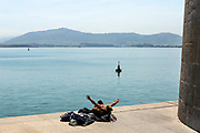 SANTANDER, SPAIN - April 17 2018 - Person jumps into the Bay of Santander on sunny day with view looking out to Somo beach and waterfront, Cantabria, Northern Spain, Europe.