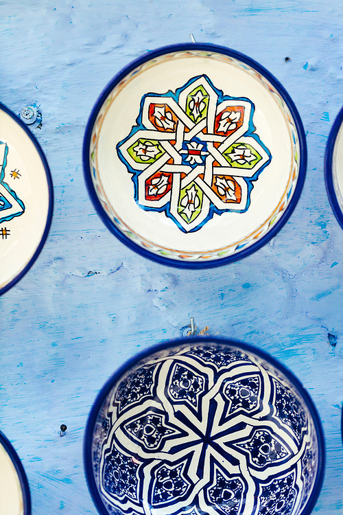 CHEFCHAOUEN, MOROCCO - 27th APRIL 2016 -  Decorative ceramic serving bowls and plates hang for sale on the blue walls of the Chefchaouen Medina - the blue city - Rif Mountains, Northern Morocco.