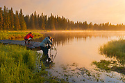 Photographers in Whirlpool Lake at dawn<br />Riding Mountain National Park<br />Manitoba<br />Canada
