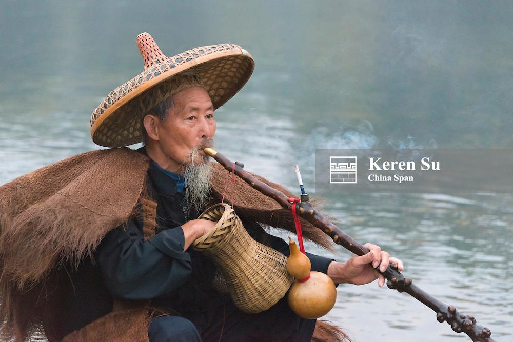 Fisherman smoking piple on bamboo raft on Li River at dawn, Yangshuo, Guangxi Province, China