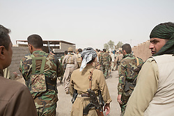 © Licensed to London News Pictures. 11/09/2015. Kirkuk, Iraq. Kurdish peshmerga fighters walk through the, previously Islamic State held, village of Zankhar. The village was captured during a peshmerga offensive to expand a safety zone around the city of Kirkuk, Iraq.<br /> <br /> The offensive, which went unchallenged after ISIS left the area ahead of the attack, saw the peshmerga capture 15 villages along the Kirkuk front line. The objective of the offensive was to expand the safety zone around Kirkuk, stopping militants from firing missiles and rockets in to the city of Kirkuk. 3 peshmerga were killed and 24 wounded due to improvised explosive devices left behind by the militants. Photo credit: Matt Cetti-Roberts/LNP