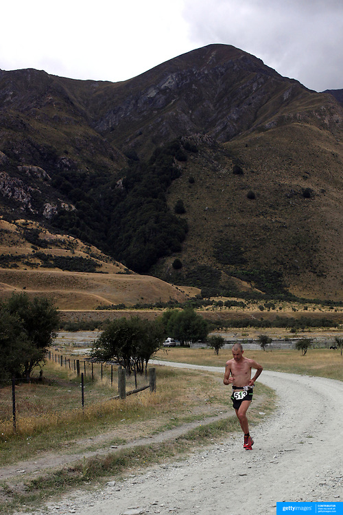 Runner Martin Cox from Great Britain crosses  Moke Creek on the Ben Lomond High Country Station on his way to winning the Pure South Shotover Moonlight Mountain Marathon and trail runs. Moke Lake, Queenstown, New Zealand. 4th February 2012. Photo Tim Clayton