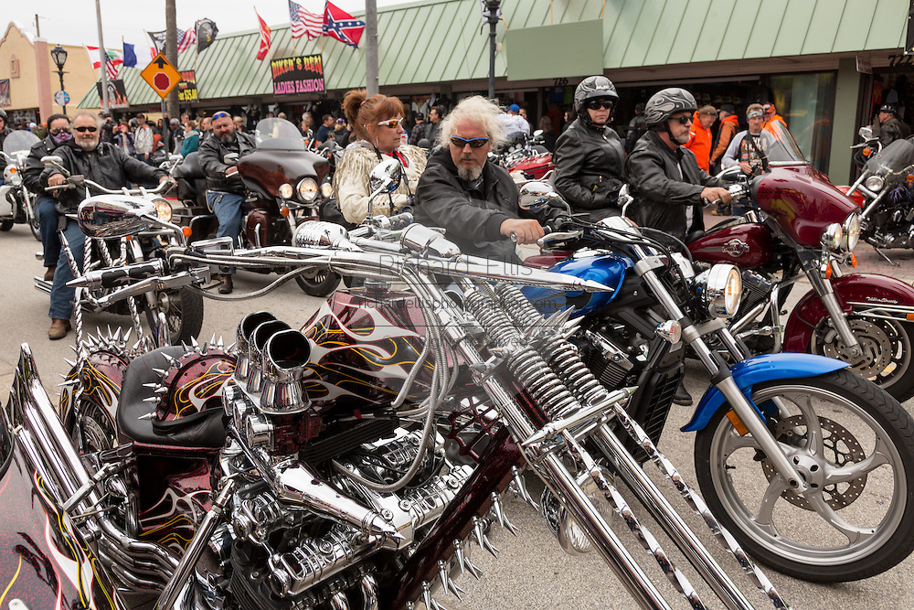 Leather clad bikers ride down Main Street past a customized Harley-Davidson chopper during the 74th Annual Daytona Bike Week March 7, 2015 in Daytona Beach, Florida.