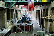 Turbines inside Hoover Dam, also known as Boulder Dam, are creating electric power, in the Black Canyon of the Colorado River, forming Lake Mead, on the border between Nevada and Arizona, USA. Constructed between 1931 and 1936 by President Franklin D. Roosevelt, its construction was the result of a massive effort involving thousands of workers. Lake Mead is 180 km long, and when filled to capacity can reach 28 million acre-feet of water. However, the lake has not reached this capacity in more than a decade, due to increasing droughts.