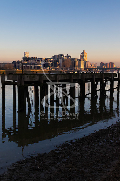 London, February 24th 2016. Pilings from an old dock are reflected in the River Thames as apartment buildings in Chelsea are illuminated by the first rays of sunshine as the sun rises on a chilly but clear London morning. ///FOR LICENCING CONTACT: paul@pauldaveycreative.co.uk TEL:+44 (0) 7966 016 296 or +44 (0) 20 8969 6875. ©2015 Paul R Davey. All rights reserved.