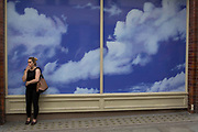 A smoker stands in front of a construction hoarding featuring cloud and sky patterns, on 31st July 2017, in Covent Garden, London, England.