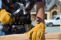 Construction worker hammering nail to wooden plank on construction site