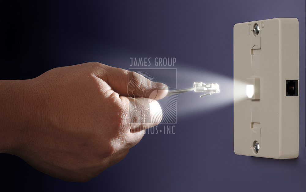 hand plugging an ethernet cable into a glowing port mounted to a wall