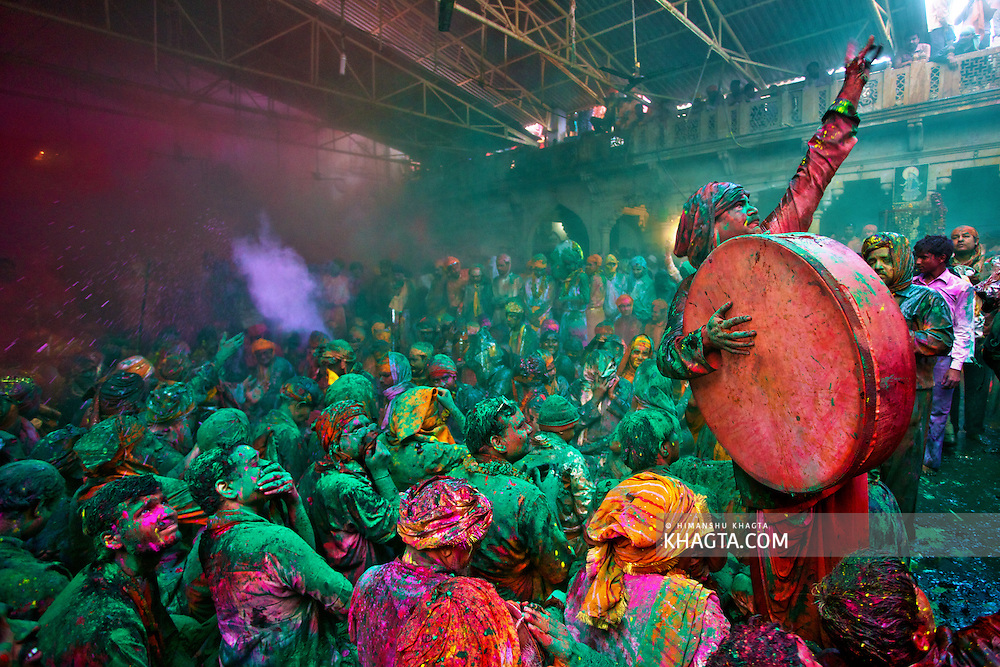 People of village Barsana, including a drummer, sitting together in an event called the 'Samaaj', warning a child throwing water at them while celebrating the festival of colors, Holi in braj region of Mathura.