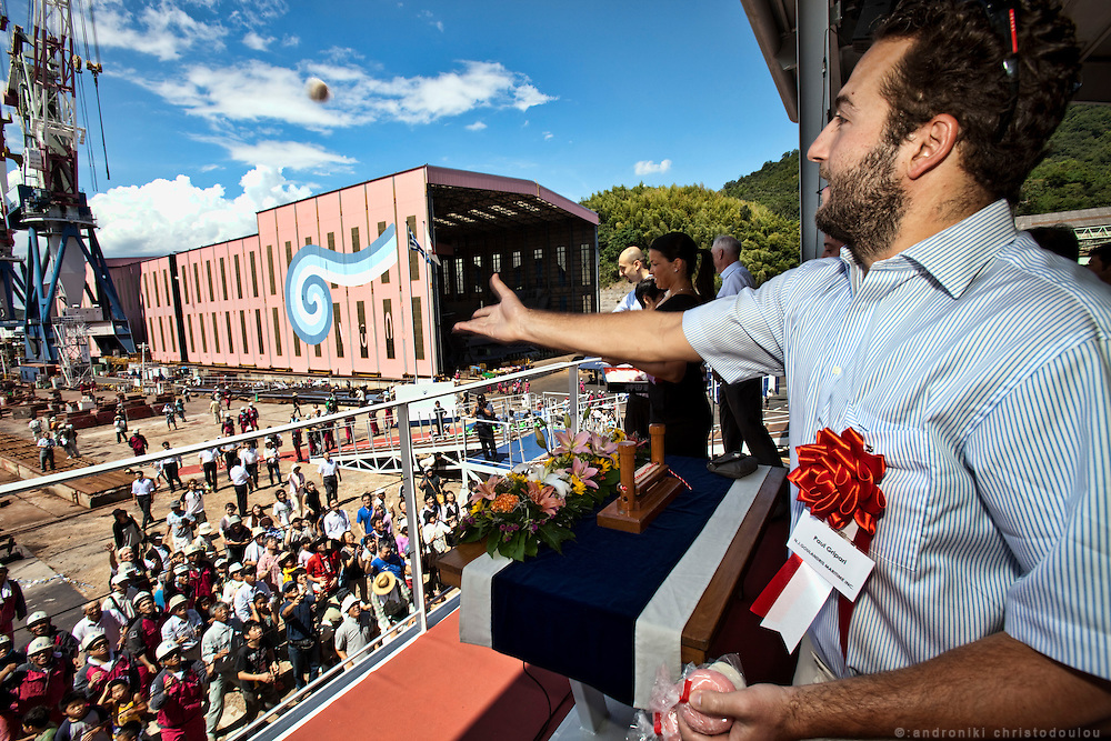 """Paul Gripari throwing """"motsi"""" (Japanese rice-cake that is a local custom to throw in launcing ceremonies) to people who attented the launching and naming ceremony of the ship ATTALIA,"""
