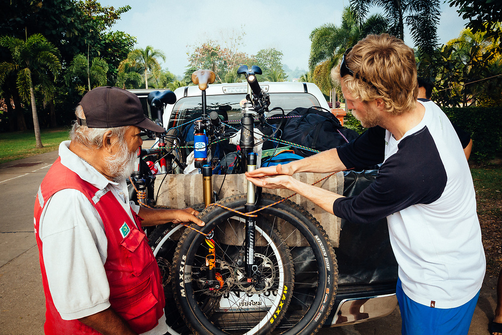 Andrew Whiteford explains how our bikes work to a local farmer along the road to Doi Bakia in the jungle near Chiang Dao, Thailand.
