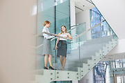 Businesswomen conversing on steps in office