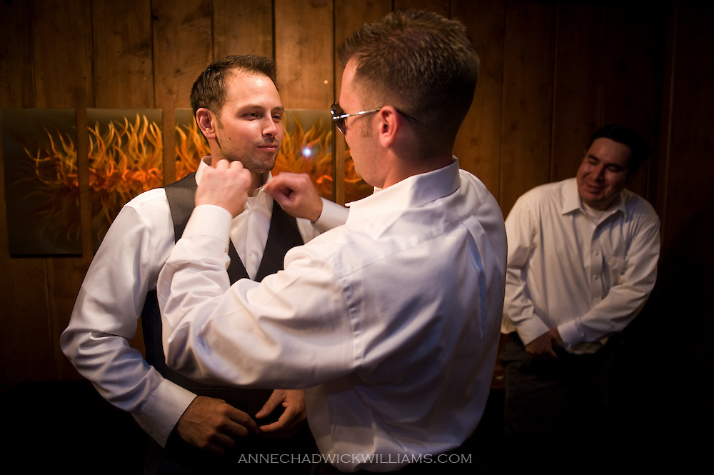 Groom has help with shirt from groomsman.