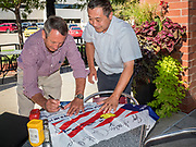 23 SEPTEMBER 2019 - DES MOINES, IOWA: MARK SANFORD, left, the former Republican Governor of South Carolina and six term Congressman from South Carolina, autographs a flag at Zombie Burger, a Des Moines restaurant, Monday. Sanford is challenging incumbent President Donald Trump for the Republican nomination for the US presidency. Iowa hosts the first event of the presidential selection cycle. The Iowa Caucuses are scheduled for February 3, 2020.        PHOTO BY JACK KURTZ