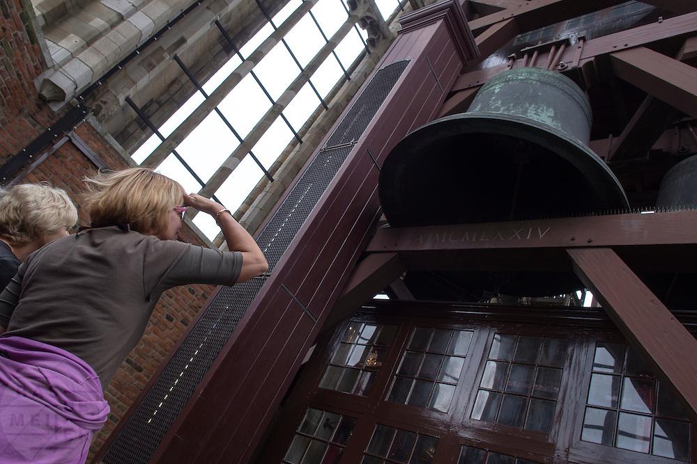 Bezoekers van de Domkerk bekijken het carrillion van de kerktoren.<br /> <br /> Visitors at a tour in the Dom tower are watching the bells in the tower.