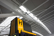 "Seen from ground level, we see one of the giant 'hand nodes' of Heathrow Airport's Terminal 5 roof structure. Developed by Arup to design the geometry of abutment steel supports, this engineering challenge needed to help support 50 ton tusk rafters to made T5 the largest free-standing building in the UK. A large H denotes the check-in zone for international passengers. The main architecture was created by the Richard Rogers Partnership (now Rogers Stirk Harbour and Partners) and opened in 2008 after a cost of £4.3 billion. Terminal 5 has the capacity to serve around 30 million passengers a year. From writer Alain de Botton's book project ""A Week at the Airport: A Heathrow Diary"" (2009)."