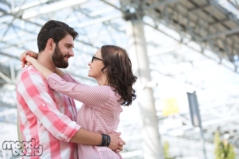 Loving couple looking at each other while embracing outside building