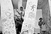 One young white female and one young white male, add drawnings to painted walls. Glastonbury 2007