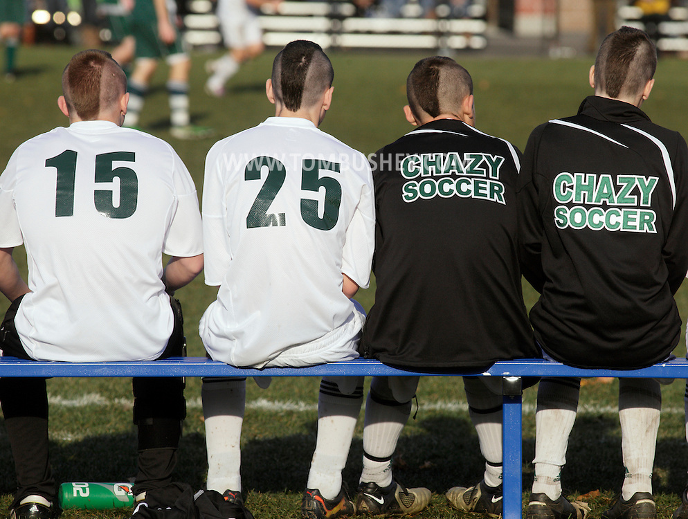 Middletown, New York  - Chazy soccer players with Mohawk haircuts sit on the bench and watch their teammate play Hamilton in the New York State Class D boys' soccer championship game on Nov. 20, 2011.