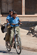Young Indian boys in school uniform riding bicycle to school in Khore village in Rajasthan, Northern India