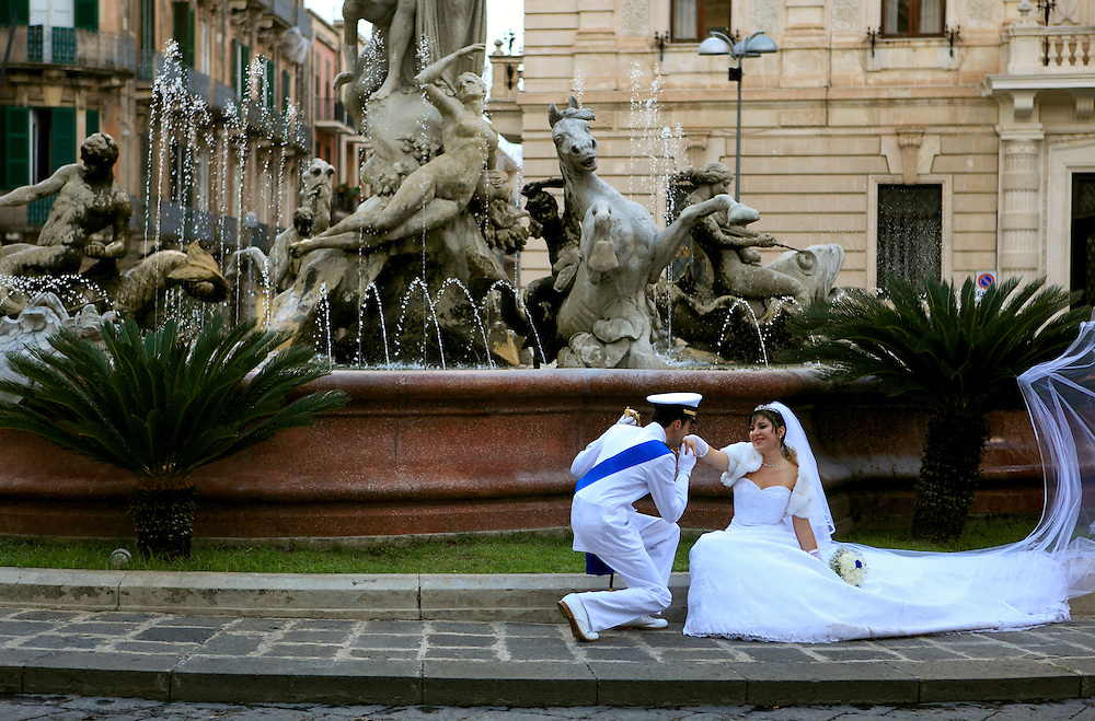 Bride and groom posing for the photographer in front of the  Fountain of Diana, Piazza Archimedes, Syracuse, Sicily. Syracuse is famous for its rich Greek history, culture, amphitheaters, architecture, and as the birthplace of Archimedes. This 2,700 year-old city played a key role in ancient times, when it was one of the top powers of the Mediterranean world.