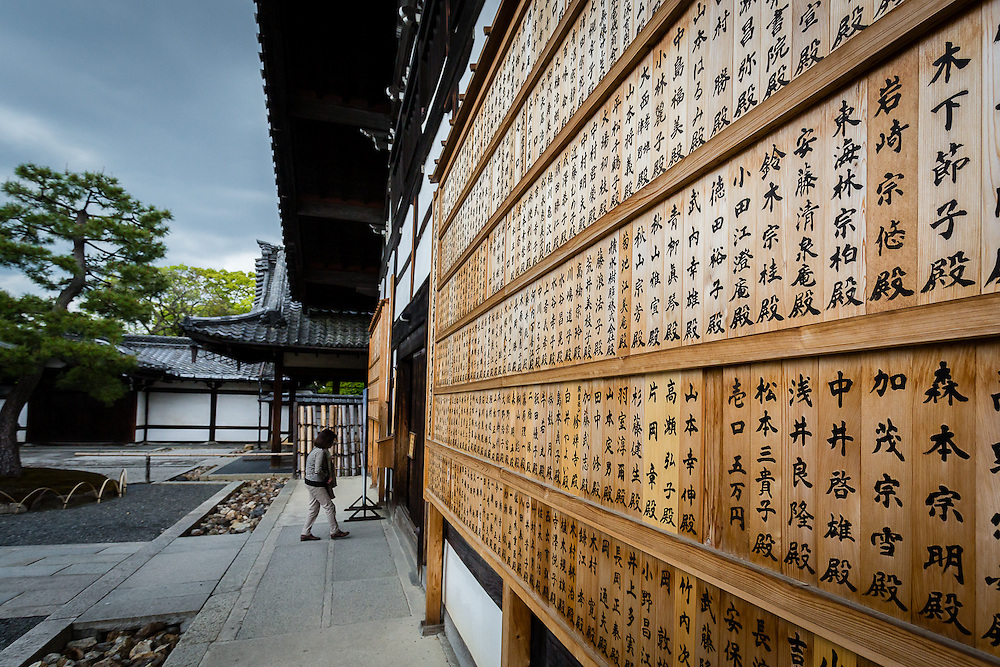 A lady enters one of the halls in Kennin-ji temple, whose wall is decorated with kanji.