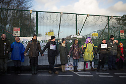 © Licensed to London News Pictures . 26/01/2014 . Salford , UK . Protesters link hands and stand in front of the gate leading to the fracking site . Protesters march to an iGas fracking exploration site at Barton Moss , Salford , today (Sunday 26th January 2014) . A long term protest camp has been established on an access road leading to the site and today (26th January) protesters from other areas of the country travelled to the site to join with other protesters against fracking . Photo credit : Joel Goodman/LNP