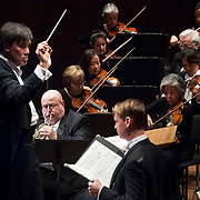 """November 21, 2013 - New York, NY : Conductor Alan Gilbert, left, leads the New York Philharmonic and soloists Philip Myers, on horn at front left, and tenor Michael Slattery, standing at foreground center, in Bejamin Britten's """"Serenade for Tenor, Horn, and Strings, Op. 31 (1943)"""" at Avery Fisher Hall at Lincoln Center on Thursday night. Slattery made his NY Phil debut as a last-minute substitution for tenor Paul Appleby, who withdrew due to illness. CREDIT: Karsten Moran for The New York Times"""