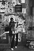 A newspaper salesman reading a newspaper, New York, USA, 1980