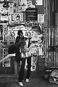 A newspaper salesman reading a newspaper, New York, USA, 1980