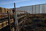 The border wall between Sasabe, Sonora, Mexico, and Sasabe, Arizona, USA, as seen from Arizona.  The border wall runs through corrals for livestock that once straddled both sides of the border.
