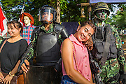 "15 JUNE 2014 - BANGKOK, THAILAND: Women pose for photos with Thai military special operations soldiers during public relations ""Return Happiness to Thais"" party in Lumpini Park in Bangkok. The Thai military junta, formally called the National Council for Peace and Order (NCPO), is sponsoring a series of events throughout Thailand to restore ""Happiness to Thais."" The events feature live music, dancing girls, military and police choirs, health screenings and free food.   PHOTO BY JACK KURTZ"